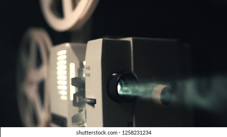 Front view of an old-fashioned antique Super 8mm film projector, projecting a beam of light in a dark room next to a stack of unraveled film reels.