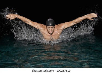 Front view of an olympic swimmer training for the butterfly stroke in a swimming pool.