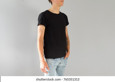 Front view on attractive and handsome young man with authentic hipster arm tattoos, in blue beanie, in black mockup simple tshirt from organic cotton, isolated on white background