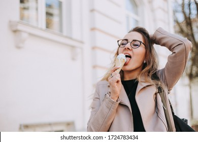 front view on beautiful girl in glasses eating an ice cream outdoors on spring