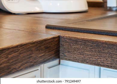 Front view on corner of two flat wooden boards with wood texture and edges lit with natural and artificial light, FOCUS ON BOARDS CORNER