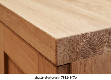 Front view on corner of wooden bathroom table with door made of three flat wooden boards with wood texture and edges lit with artificial light, FOCUS ON CORNER