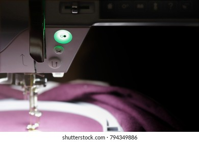 front view on machine head of embroidery machine in dark light mood with bright illuminated blurred working area with needle, claret red fabric and hoop - shallow depth of field - copy space for text