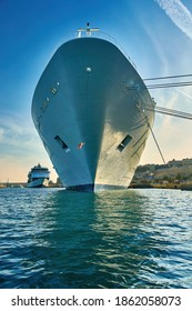 Front view on a ocean liner moored in the port of ancient Valletta. View from the water surface on the nose of a huge white ship against the blue sky. Malta.