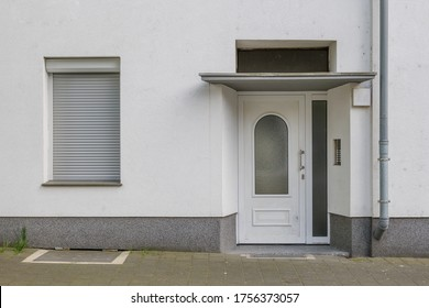 Front view on sidewalk of typical facade with swing door, canopy and windows at the entrance of residential building in Europe.