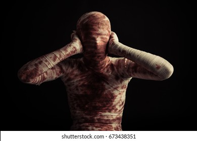Front view on single bloody mummy with hands on hears over black background for scary Halloween scene