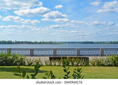Front view on the Volga quay of the Samara. Green grass on city embankment, beautiful sky with cumulus clouds on sunny summer day