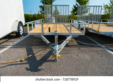 Front View of a Open Flat Bed Utility Trailer Parked Next to a Cargo Trailer