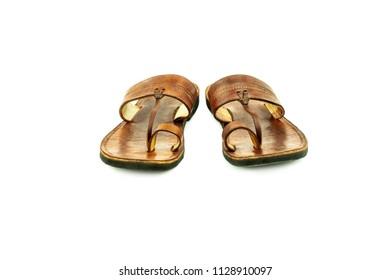 Front view of a pair of brown traditional indian leather sandals isolated on white background.
