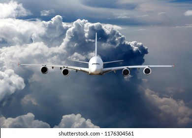 Front view of the passenger aircraft in flight. Thunderclouds in the background.