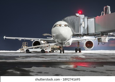 Front view of the passenger aircraft stands at the jetway on night airport apron. The baggage compartment of the airplane is open and the luggage is being loaded