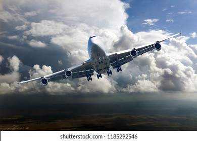 Front view of the passenger plane in flight. Left heeling of aircraft. Thunderclouds in the airplane background.
