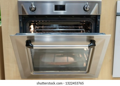 Front view photo of open door on new and modern built-in oven