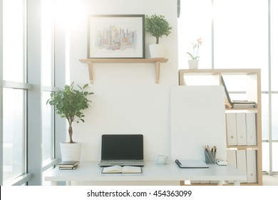 Front view picture of studio workplace with blank notebook, laptop. Designer comfortable work table, home office.