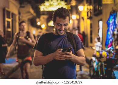 front view picture of young smiling man using smartphone at night in a busy city street, hipster guy chatting with friends at social networks via cellphone outdoor, smiling and happy