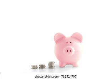 Front view. Pink piggy bank and coins isolated on white