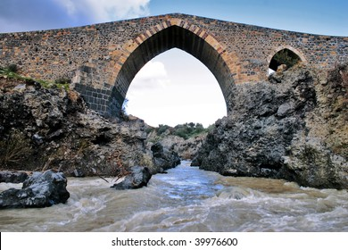 """Front view of the """"ponte dei saraceni"""", an ancient medieval bridge of Norman age located on the Simeto river, near Adrano - Catania, in Sicily"""