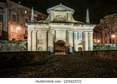 Front view of Porta San Giacomo and the walls of the upper city of Bergamo. Fortified and historical urban complex in Italy. Night cityscape.