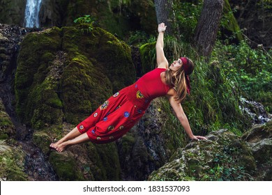 Front view portrait of adult caucasian woman 30 years old sitting on rock in nature in front of waterfall in red dress stretching in yoga pose asana - Spirituality inner peace and relaxation concept