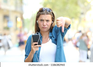 Front view portrait of an annoyed girl listening to music with thumbs down in the street