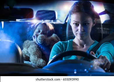 Front view. Portrait of a beautiful woman driving her car at night in the rain. In the back her little girl fell asleep her teddy in the arms