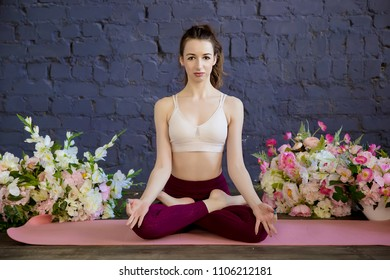 Front view portrait of beautiful young woman sitting on the sports mat, resting after doing yoga exercises, sitting in ardha Padmasana, Lotus pose, relaxing. Meditation. Lifestyle.