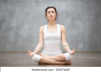 Front view portrait of beautiful young woman with floral tattoos working out against grey wall, resting after doing yoga exercises, sitting in ardha Padmasana, Lotus pose, relaxing. Full length