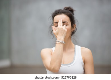 Front view portrait of beautiful young woman wearing white tank top working out against grey wall, resting after doing yoga exercises, using nadi shodhana pranayama technique. Close up