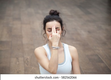 Front view portrait of beautiful young woman wearing white tank top working out on wooden floor, resting after doing yoga exercises, using Alternate Nostril Breathing technique. Close up