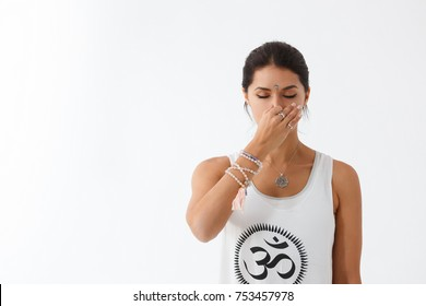 Front view portrait of beautiful young woman wearing white tank top working out against white wall, using nadi shodhana pranayama technique. Freedom, calm and yoga banner concept, copy space