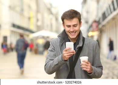 Front view portrait of a businessman walking towards camera and using a smart phone in the street in winter
