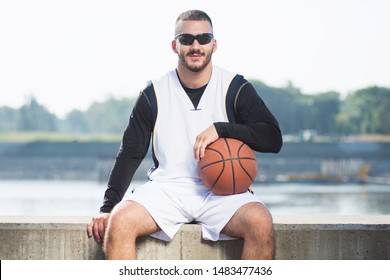 Front view portrait of cool sitting streetball or basketball player outdoors.