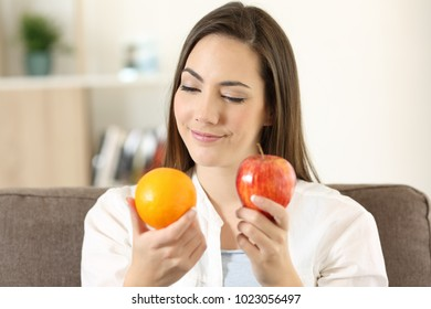 Front view portrait of a doubtful woman deciding between an orange and apple sitting on a couch at home