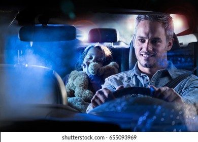 Front view. Portrait of a handsome man driving his car at night in the rain. In the back his little girl fell asleep her teddy in the arms