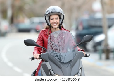 Front view portrait of a happy bker driving a motorbike on the street