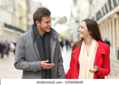 Front view portrait of a happy couple walking and talking in winter in the street