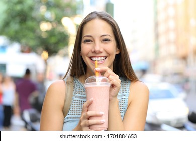 Front view portrait of a happy girl looking camera drinking milkshake in the street