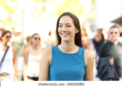 Front view portrait of a happy girl walking between other people on the street