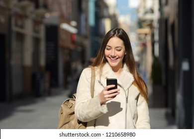 Front view portrait of a happy lady using a smart phone in winter in the street