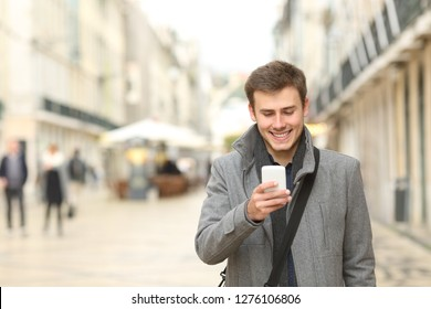 Front view portrait of a happy man walking checking smart phone in the street