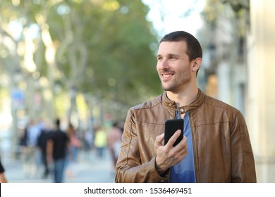 Front view portrait of a happy man holding smart phone walking towards camera looking at side in the street
