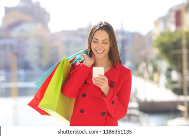 Front view portrait of a happy shopper tourist using a smart phone holding shopping bags in winter holiday