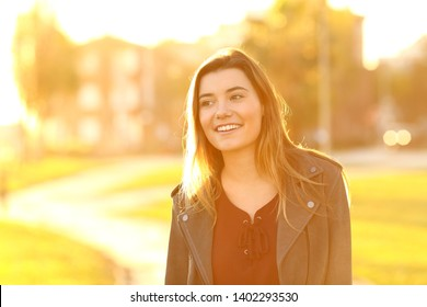 Front view portrait of a happy teen distracted walking in the street at sunset