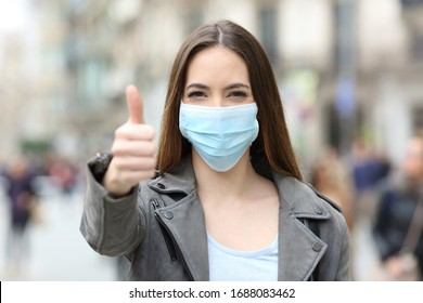 Front view portrait of a happy woman with protective mask gesturing thumbs up in the street