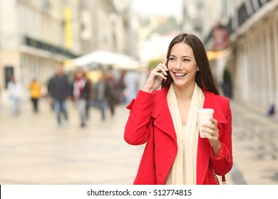 Front view portrait of a happy woman calling on the mobile phone walking towards camera in the street
