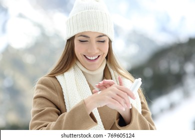 Front view portrait of a happy woman applying moisturizer cream to hydrate hands with a snowy mountain in the background