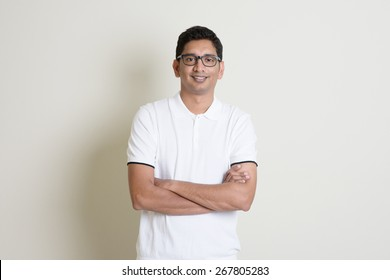 Front view portrait Indian guy arms crossed, standing on plain background with shadow and copy space.