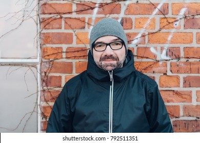 Front view portrait of a middle-aged bearded man smiling while wearing waterproof black jacket, eyeglasses and gray hat outdoors against brick wall