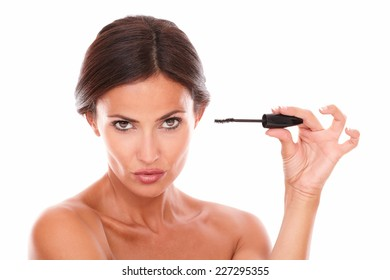 Front view portrait of pretty seductive woman with mascara showing her sensual look with nude shoulders while looking at camera on isolated studio