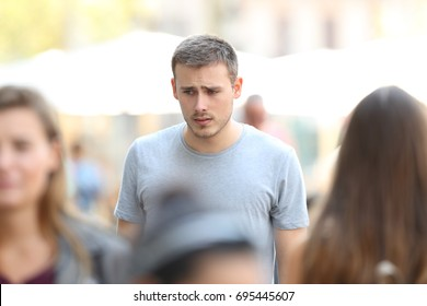Front view portrait of a sad boy walking on the street